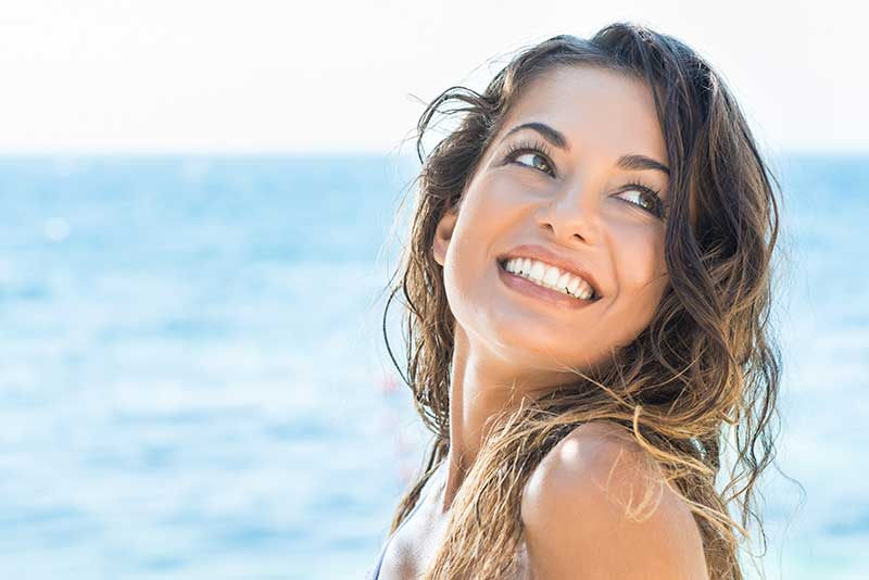 A lady on a beach displaying a lovely smile made of veneers in Salinas, CA